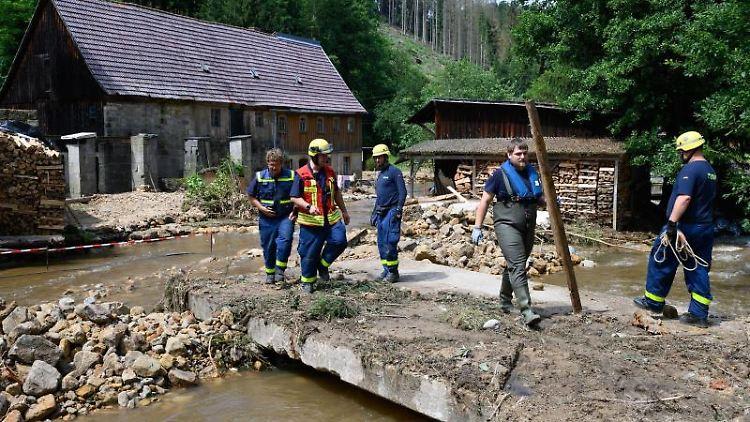 Einsatzkräfte Technisches Hilfswerk beseitigen am Krippenbach im Juli Geröll. Foto: Robert Michael/dpa-Zentralbild/dpa