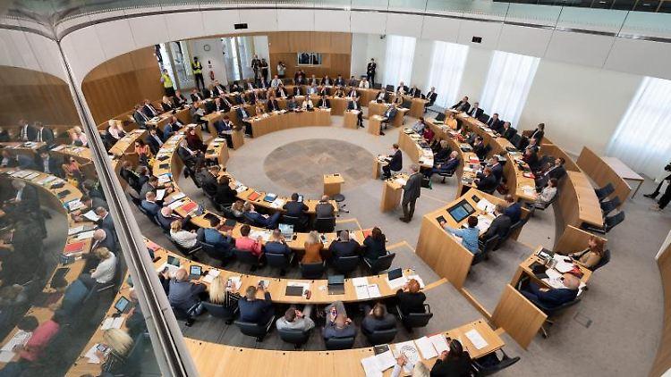 Mitglieder des Landtags von Rheinland-Pfalz sitzen während einer Sitzung auf ihren Plätzen. Foto: Sebastian Gollnow/dpa