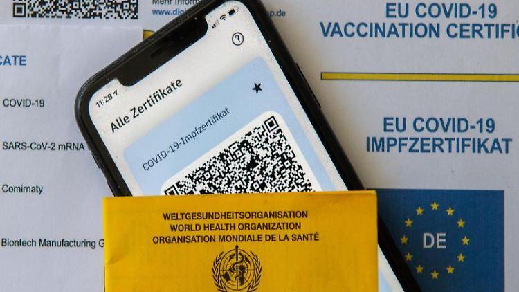 Ein Impfpass und ein Smartphone mit der CovPass-App liegen auf einem Impfzertifikat. Foto: Stefan Puchner/dpa/Symbolbild