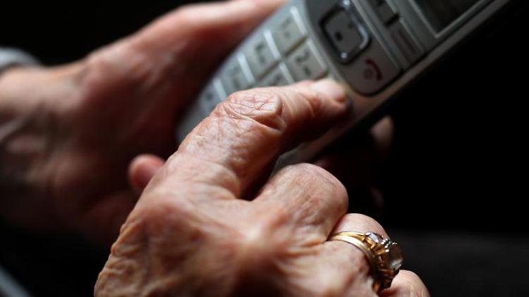 Eine ältere Frau tippt auf einem schnurlosen Festnetztelefon. Foto: Karl-Josef Hildenbrand/dpa/Symbolbild