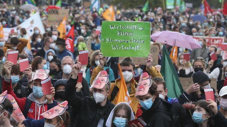 Demonstranten mit Plakaten. Foto: David Young/dpa/Symbolbild