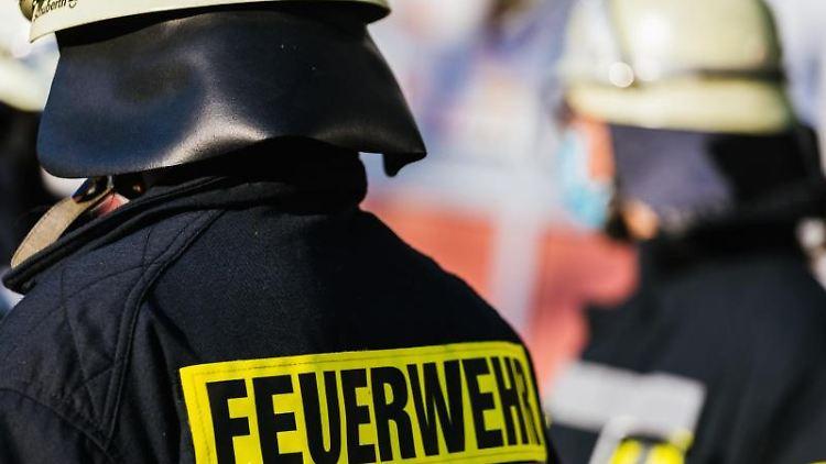 Einsatzkräfte der Feuerwehr in Schutzkleidung. Foto: Philipp von Ditfurth/dpa/Symbolbild