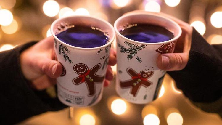 Zwei Frauen stoßen mit Glühwein gefüllten Bechern auf einem Weihnachtsmarkt an. Foto: Christoph Schmidt/dpa/Symbolbild