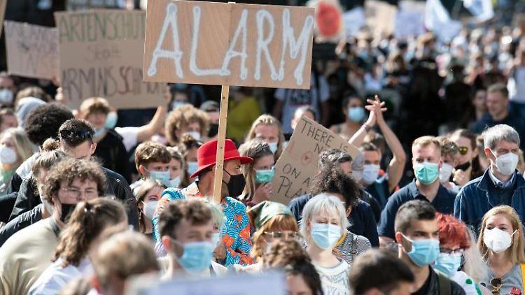 Teilnehmer halten auf der Fridays for Future-Demonstration Protestplakate in den Händen. Foto: Federico Gambarini/dpa