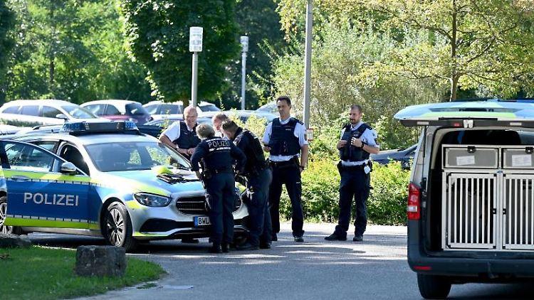 Polizisten besprechen sich vor der Klinik in Weinsberg. Foto: Bernd Weißbrod/dpa/Archivbild