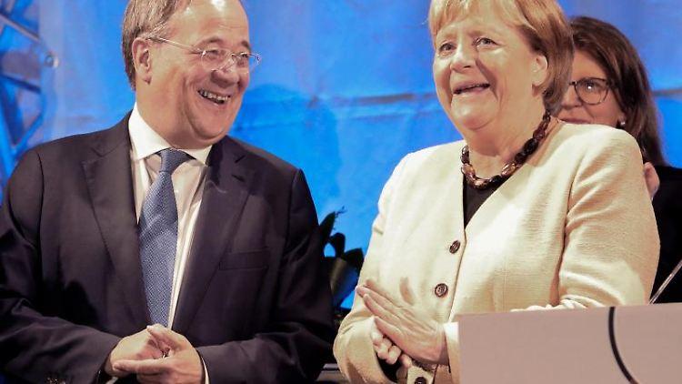Armin Laschet (l-r) und Angela Merkel stehen bei einem gemeinsamen Wahlkampfauftritt auf der Bühne. Foto: Bernd Wüstneck/dpa-Zentralbild/dpa/Archivbild