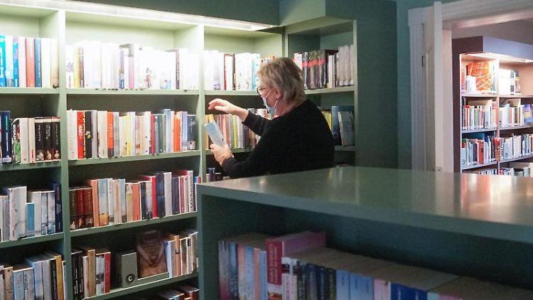 Bibliotheksleiterin Georgia Arndt sortiert im Grünen Salon der Wittstocker Stadtbibliothek die Bücher. Foto: Christian Bark/dpa-Zentralbild/dpa/Archivbild