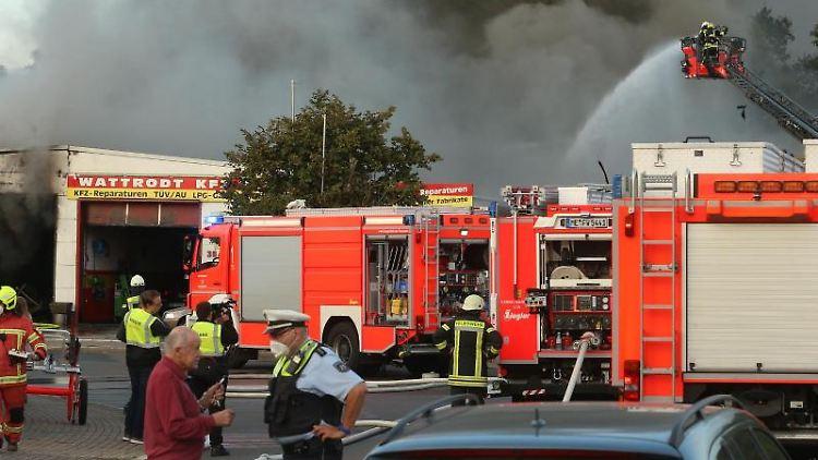 Einsatzkräfte der Feuerwehr löschen einen Brand in einer Kfz-Werkstatt in Langenfeld. Foto: David Young/dpa