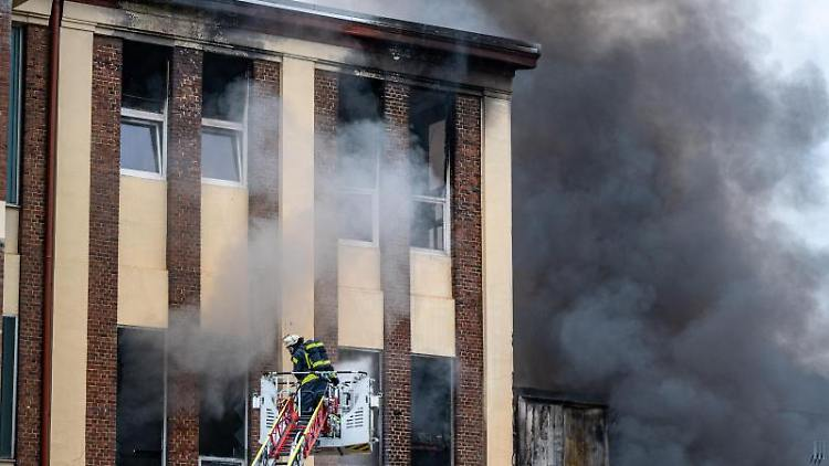 Dichte Rauchwolken steigen aus der brennenden Stahlfabrik. Foto: Markus Klümper/dpa