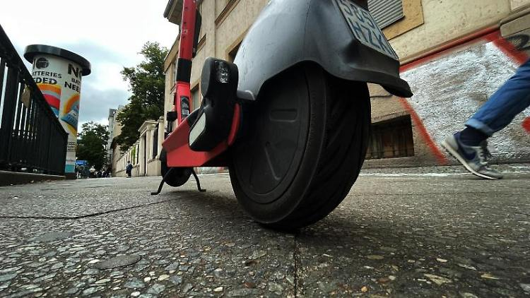 Ein E-Scooter steht mitten auf einemGehweg in Neukölln. Foto: Paul Zinken/dpa