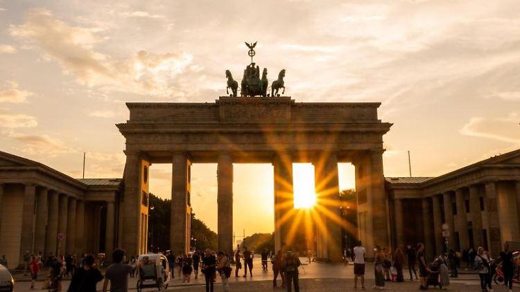 Die Sonne geht hinter dem Brandenburger Tor unter. Foto: Christophe Gateau/dpa