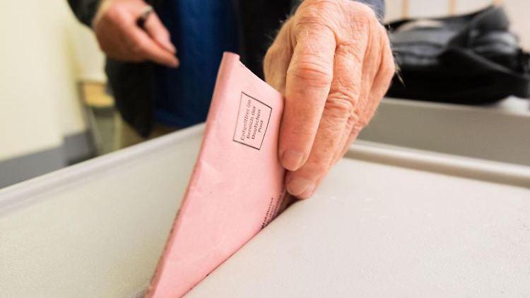 Ein Mann wirft seinen Stimmzettel für die Bundestagswahl in eine Urne. Foto: Julian Stratenschulte/dpa/Archivbild
