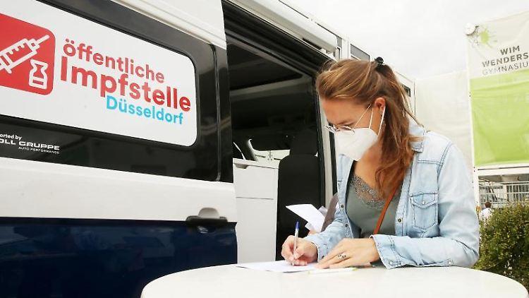 Vor einem Wahllokal füllt eine Frau einen Fragebogen an einer mobilen Impfstation aus. Foto: David Young/dpa