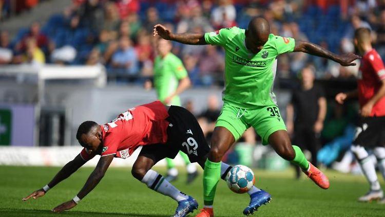 Hannovers Gaël Ondoua (l) und Sandhausens Charlison Benschop kämpfen um den Ball. Foto: Daniel Reinhardt/dpa