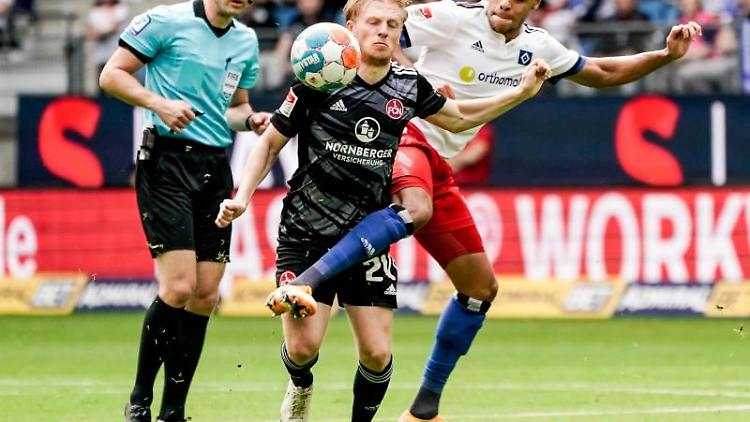 Nürnbergs Mats Moller Daehli (l) und Hamburgs Jan Gyamerah kämpfen um den Ball. Foto: Axel Heimken/dpa