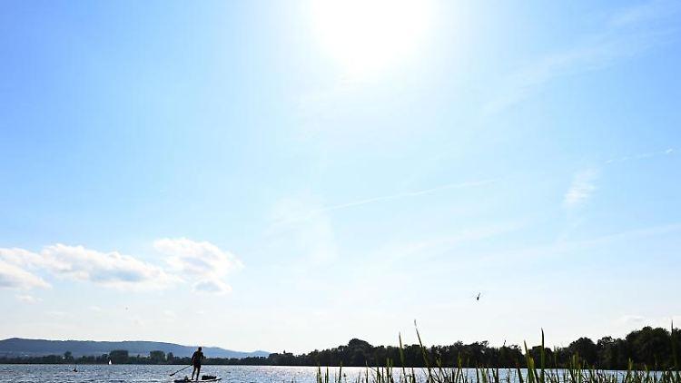 Ein Stand-Up-Paddler ist auf dem Northeimer Freizeitsee bei Sonnenschein unterwegs. Foto: Swen Pförtner/dpa