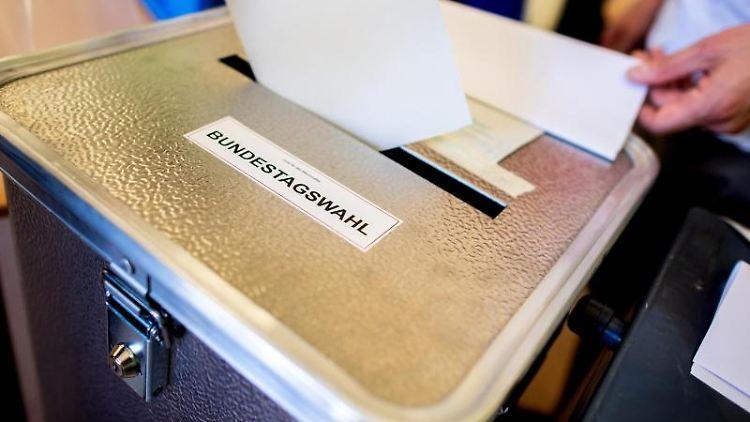 Ein Wähler wirft in einem Wahllokal seinen Wahlzettel ein. Foto: Hauke-Christian Dittrich/dpa