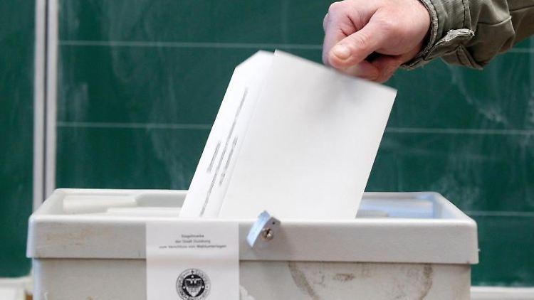 Ein Wähler wirft seinen Stimmzettel in einem Wahllokal in die Wahlurne. Foto: Roland Weihrauch/dpa