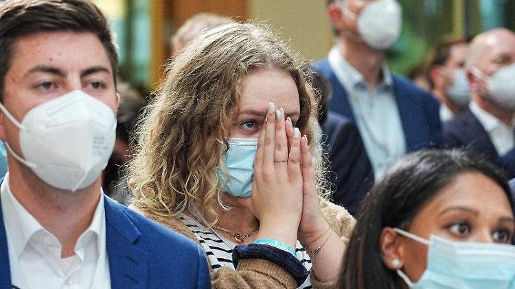 Unterstützer der CDU / CSU reagieren nach der Bekanntgabe der ersten Prognosen. Foto: Michael Kappeler/dpa