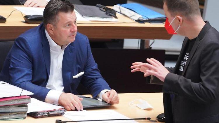 Andreas Geisel (l, SPD), Innensenator, und Klaus Lederer (Die Linke) unterhalten sich. Foto: Jörg Carstensen/dpa