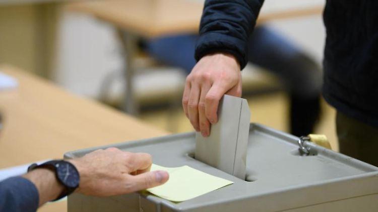 Ein Wähler wirft bei der Stimmabgabe seinen Stimmzettel in eine Wahlurne. Foto: Robert Michael/dpa-Zentralbild/dpa