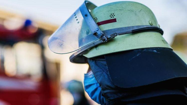 Ein Feuerwehrmann mit Helm und Maske. Foto: Philipp von Ditfurth/dpa/Symbolbild