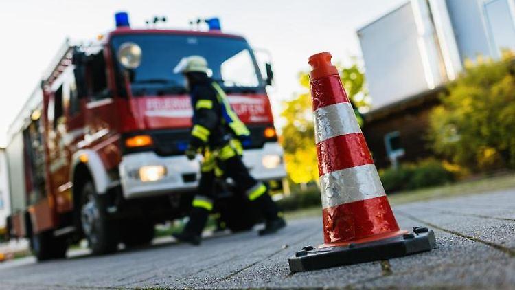 Ein Feuerwehrmann geht an einem Einsatzfahrzeug vorbei. Foto: Philipp von Ditfurth/dpa/Symbolbild