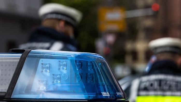 Zwei Polizeibeamte stehen vor einem Einsatzwagen. Foto: Philipp von Ditfurth/dpa/Symbolbild