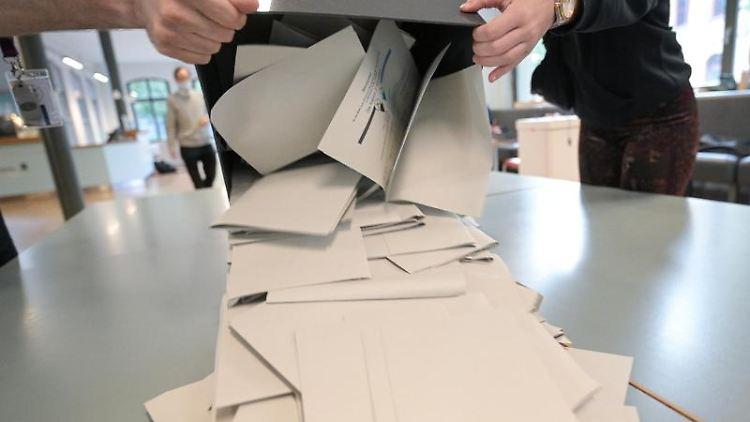 Wahlhelfer schütten in einem Wahllokal Stimmzettel für die Bundestagswahl aus. Foto: Sebastian Gollnow/dpa/Symbolbild