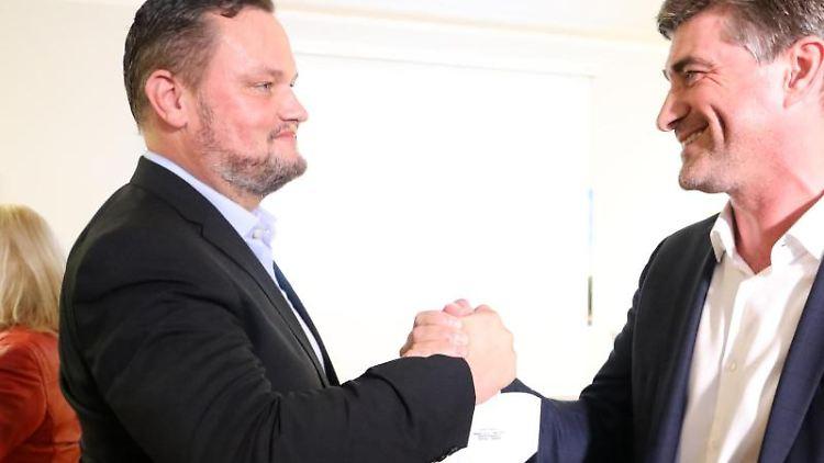 Rene Domke (l-r), Spitzenkandidat der FDP für die Landtagswahl in Mecklenburg-Vorpommern, und Hagen Reinhold (FDP), Bundestagsmitglied, beglückwünschen sich zu dem Wahlergebnis. Foto: Bernd Wüstneck/dpa-Zentralbild/dpa