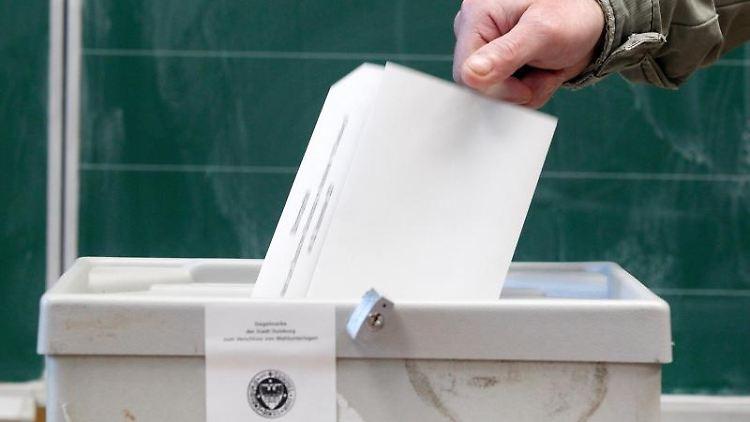 Ein Wähler wirft seinen Stimmzettel in einem Wahllokal in die Wahlurne. Foto: Roland Weihrauch/dpa/Symbolbild