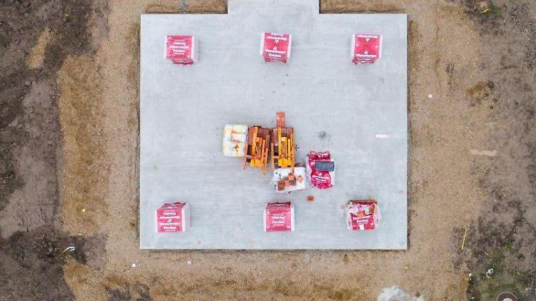 Baumaterial für ein Einfamilienhaus liegt auf einer Bodenplatte. Foto: Julian Stratenschulte/dpa/Symbolbild