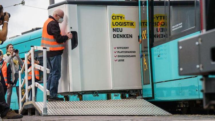 Mitarbeiter der Frankfurter Verkehrsgesellschaft (VGF) verladen einen Container in eine Straßenbahn. Foto: Frank Rumpenhorst/dpa