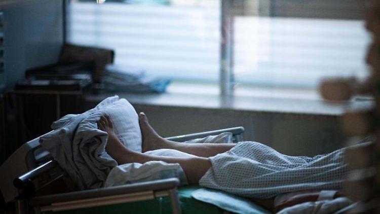 Ein Patient liegt im Zimmer einer Corona-Intensivstation. Foto: Fabian Strauch/dpa/Symbolbild