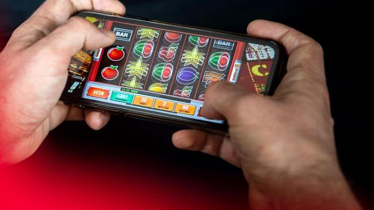 Auf einem Smartphone spielt ein Mann ein Online-Spiel. Foto: Sina Schuldt/dpa/Symbolbild