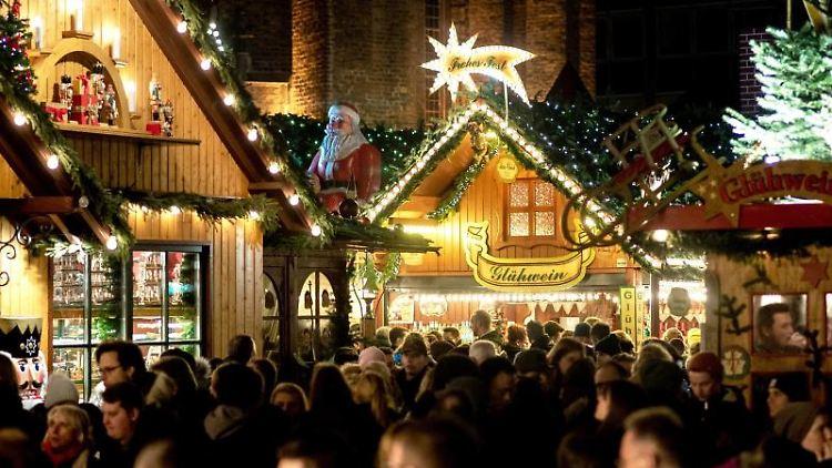 Besucher gehen über den Weihnachtsmarkt nahe der Marktkirche in der historischen Innenstadt. Foto: Hauke-Christian Dittrich/dpa/Archivbild