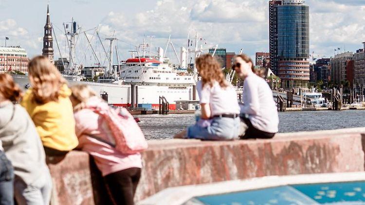 Junge Menschen sitzen bei schönem Wetter an der Elbe. Foto: Markus Scholz/dpa/Symbolbild