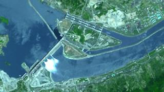 Das Drei-Schluchten-Projekt dient der Flutkontrolle und Energiegewinnung. Auf Satellitenaufnahmen sind die Dammanlagen deutlich zu erkennen. 1994 wurde mit dem Bau der gewaltigen Talsperre begonnen.