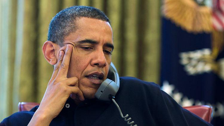 Obama telefoniert an seinem Schreibtisch im Weißen Haus.