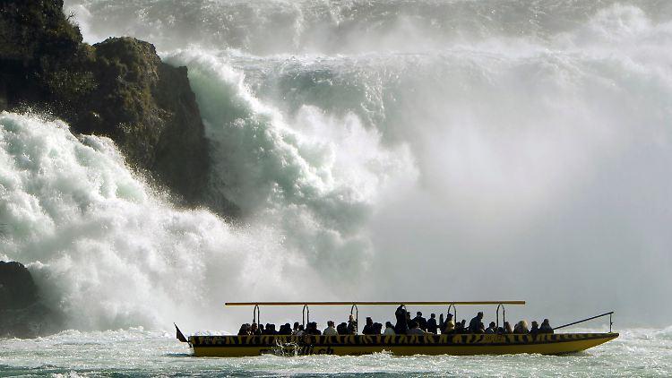 Naturspektakel auf dem Rhein: Im schweizerischen Neuhausen betrachten Touristen vom Boot aus einen Wasserfall im Fluss.